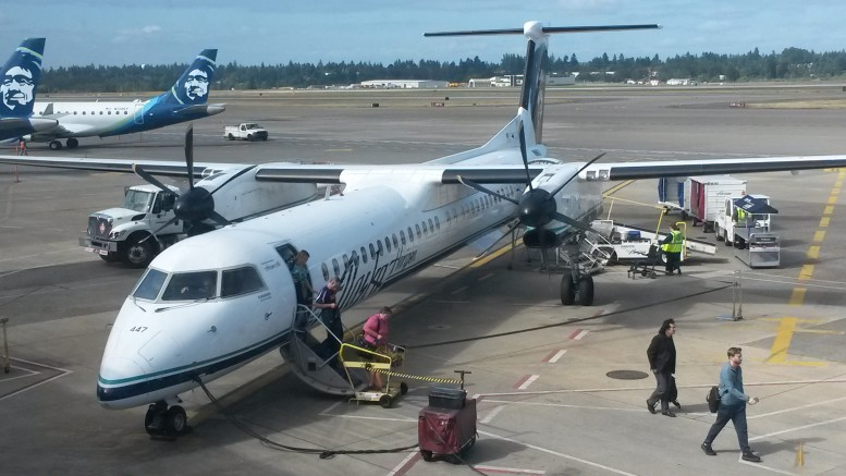 An Alaska/Horizon Air Q400 Dash 8 sits at Alaska's regional aircraft ground loading complex as its passengers head for the main terminal