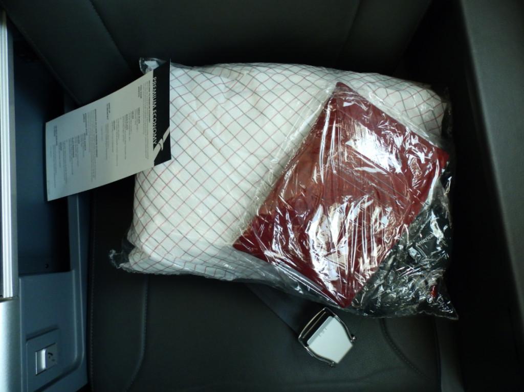 American premium economy pillow, blanket, amenity kit, and menu